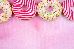 Four colorful donuts on pink background with texture. Royalty Free Stock Images