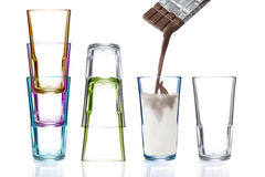 Four colorful drinking glasses, one being filled with chocolate milk Stock Image