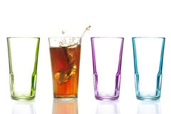 Four colorful drinking glasses, one with cola Stock Photos