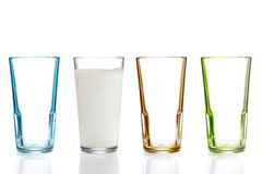 Four colorful drinking glasses, one with milk Royalty Free Stock Photos