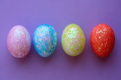 Four colorful Easter eggs on purple background. Four sparkle holiday Easter eggs on blue pink yellow red. above shot with a purple background royalty free stock photo