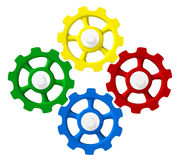 Four Colorful Gears in Sync. Red, yellow, blue and green gears on white Royalty Free Stock Photo