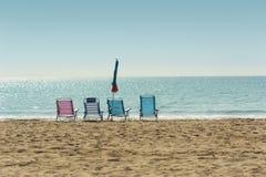 Colorful hammocks and closed umbrella in empty sandy beach. Four colorful hammocks and one closed umbrella in an empty sand beach against the calm sea horizon on Stock Image