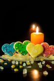 Four colorful heart cookies with cookie dough and a candle, in f Stock Images