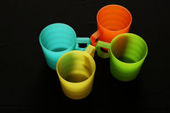 Four colorful mugs. Mugs of different colors on the black background Stock Photos