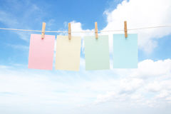Four colorful pastel notes on pegs Stock Image