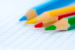 Four colorful pencils on squared paper stock photos
