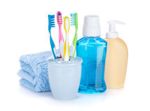 Four colorful toothbrushes, cosmetics bottles and towel Royalty Free Stock Photography