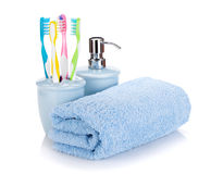 Four colorful toothbrushes, liquid soap and towel Stock Photos