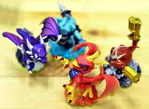Four colorful toy dragons appear in a game of fighting. Stock Photography