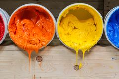 Four colors of ink for print tee shirt flowed out of barrel. Yellow orange and red colors of plastisol ink flowed out of the barrel. plastisol ink is specially Stock Photo