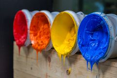 Four colors of ink for print tee shirt flowed out of barrel. Yellow orange and red colors of plastisol ink flowed out of the barrel. plastisol ink is specially Stock Image