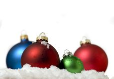 Four coloured christmas balls in the snow Royalty Free Stock Photos