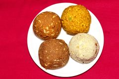 Four coloured Laddu: Indian party sweet. Made with gram-flour, semolina, dry fruits, sugar and ghee stock photo