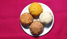 Four coloured Laddu: Indian party sweet. Made with gram-flour, semolina, dry fruits, sugar and ghee royalty free stock photos