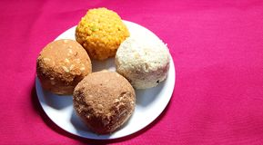 Four coloured Laddu: Indian party sweet. Made with gram-flour, semolina, dry fruits, sugar and ghee stock photos