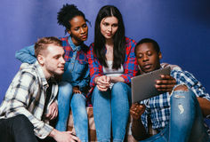 Four concentrated friends watch video on tablet Stock Photos