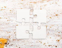 Four connected white puzzle pieces on table Royalty Free Stock Photography