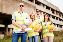 Architects Team. Four construction architects in front building damaged in the disaster. Looking at camera. Selective focus Royalty Free Stock Images
