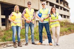 Successful Architects Team. Four construction architects in front building damaged in the disaster. Looking at camera. Selective focus Royalty Free Stock Photo