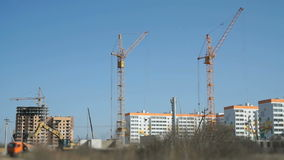 Four construction crane, excavator, truck. Working. The construction of a residential apartment complex. The construction site includes four construction crane stock video footage