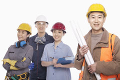 Four construction workers against white background, focus in foreground Royalty Free Stock Images