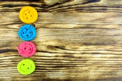 Four cookies in the form of buttons of different colors lie on a. Four round cookie in the form of buttons: yellow, blue, pink, salad flowers lie on a wooden stock photography