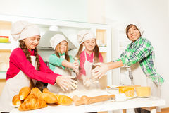 Four cooks kneads flour and eggs for bakery dough Royalty Free Stock Photography