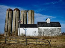 Four Corn Silos and a Barn. This is a Winter picture of a family corn farm featuring four corn silos and a weathered barn located in Elburn, Illinois in Kane stock photography