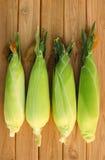 Four corn on wood table.  Stock Photo