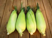 Four corn on wood table.  Stock Photos