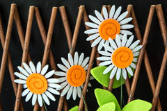 Four Daisy Flowers In Trellis Fence. Four craft felt material daisy flowers in wooden trellis fence on black background Royalty Free Stock Images