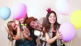 Four crazy friends having a great time in photo booth stock footage