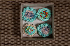 Four cupcakes with blue cream in a box. Stock Photo