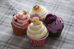 Four cupcakes on grey tablecloth Royalty Free Stock Photography