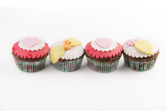 Four  cupcakes isolated on white background. Four red cupcakes isolated on white background Royalty Free Stock Images
