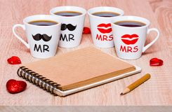 Four cups of coffee for friends, notepad, pencil and hearts Stock Photos