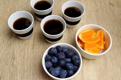 Four cups of coffee and healthy fruit snack stock image