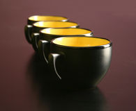 Four cups on desk Stock Photos