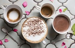 Four cups of hot aromatic coffee and chocolate. Belgian hot chocolate, espresso, espresso macchiato and latte. On the background o royalty free stock photography