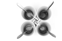 Four cups and spoons. Isolated on white background Stock Photos