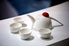 Four cups and a teapot on the table. Gorgeous, the modern style of the teapot Stock Photos