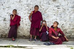 Bhutanese young novice monks play game , Bhutan. Four cute Bhutanese young novice monks playing game . boys make masks themselves with paper of notebook stock photos
