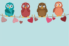 Four cute colored owlet sitting on a string. A red hearts Royalty Free Stock Images
