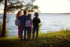 Four cute little sibling standing by the lake enjoying beautiful sunset view. Children exploring nature. Family activities in summer Royalty Free Stock Photo