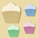 Four cute multicoloured cupcake stickers. On a beige polkadot background with dpor shadows Stock Images