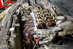 Four-cylinder car engine. With cover off under open car hood Stock Photos