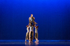 Four dancers  pose against dark blue background on stage Royalty Free Stock Images