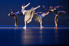 Four dancers in standing leg pose against dark blue background on stage Stock Photo