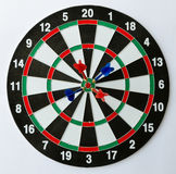 Four darts on a bullseye. Dartboard with four darts on the bulls eye Stock Image